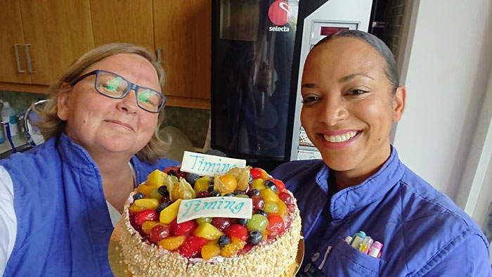 Två sjuksköterskor håller i en frukttårta som det stårt TIMING på