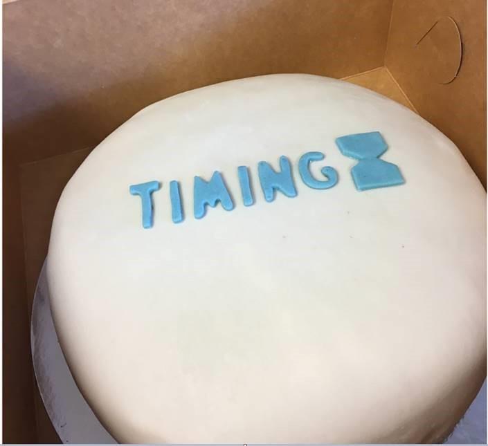 Tårtkalas i Umeå, vit tårta med blå text som det står TIMING på